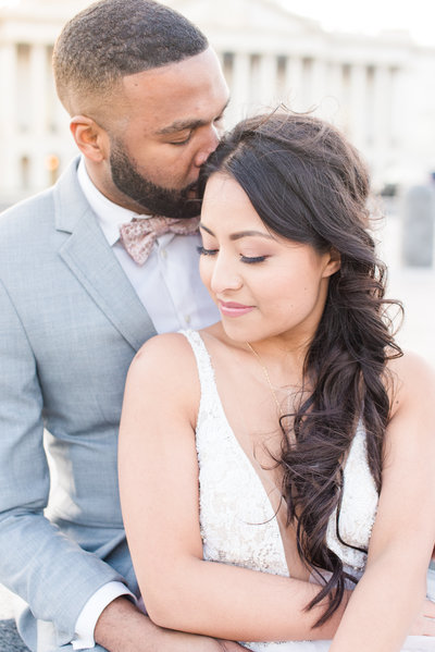 Groom kissing bride's forehead outside US Capitol