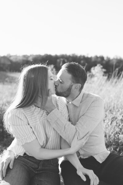 black and white photo of engaged couple kissing in a field