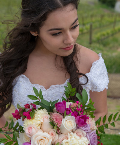 Brunette bride with purple and brown shadows rosy cheeks and pink lips black liner and mascara with false eyelashes
