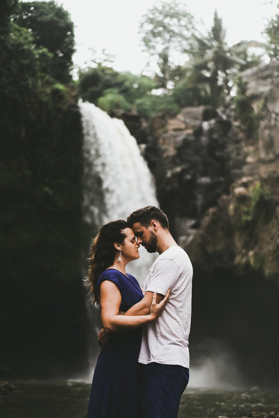 husband and wife resting foreheads together in front of waterfall