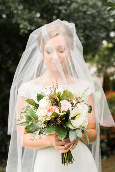 bride under veil with bouquet