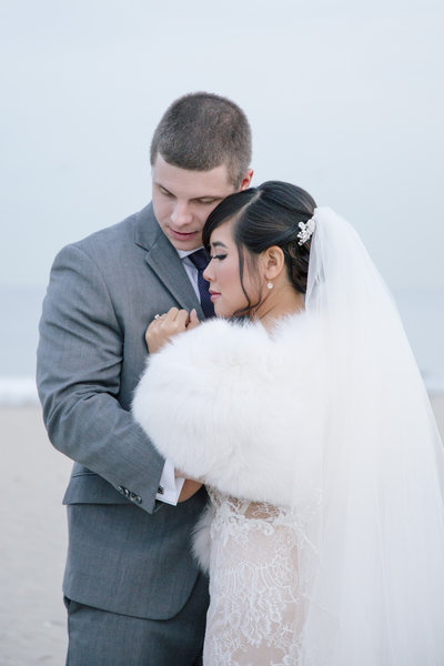 bride and groom holding each other on cold beach