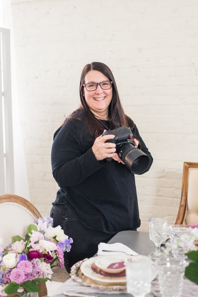 a female wedding photographer photographing a romantic and lush reception table Greensboro NC