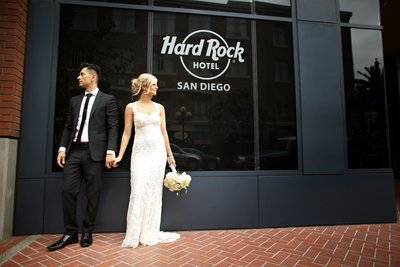 Bride and Groom holding hands in front of Hard Rock Hotel sign in Downtown San Diego