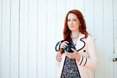 Portrait of wedding photographer holding camera.