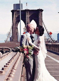 A bride and groom on Brooklyn Bridge in spring time