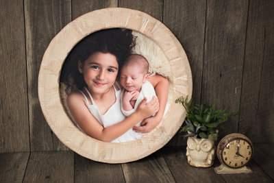 PA circular hand-carved frame photo features sister and baby brother