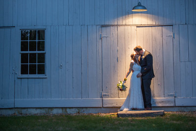 Wedding couple under barn light
