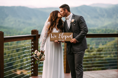 Elopement couple kissing and holding an elopement sign in Gatlinburg