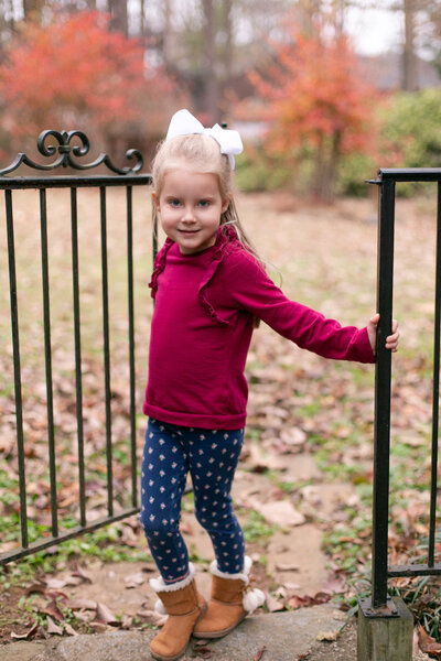 4 year old little girl wears burgundy shirt with navy leggings and boots