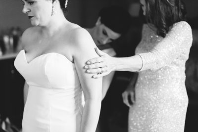 Black and white image of bride getting ready with Mom and Sister