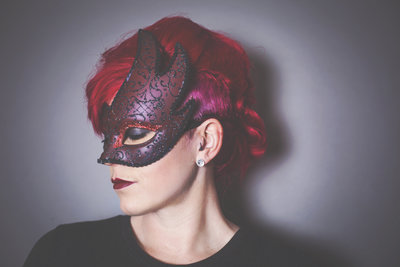 Redheaded Jessica Elisze Photographer with a  masquerade mask on.