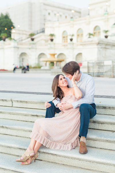 A happy couple sitting together on the steps of the Capital Building in Washington DC.
