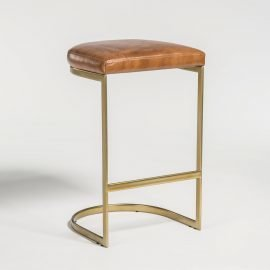 Balancing dining stool with gold base and tan leather seat from Hockman Interiors