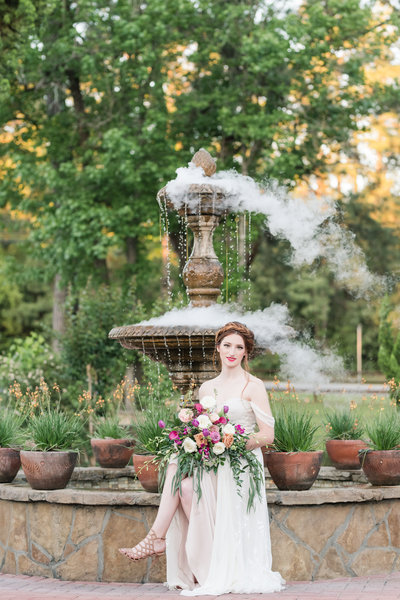 Bride sits in front of fountain at Madera Estates Wedding