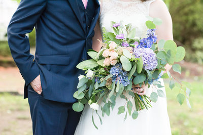 detail photograph of a bride and groom standing next to each other with the groom wearing a dark navy blue suit and the bride holding purple, green, and pink wedding bouquet at Gardens at Gray Gables