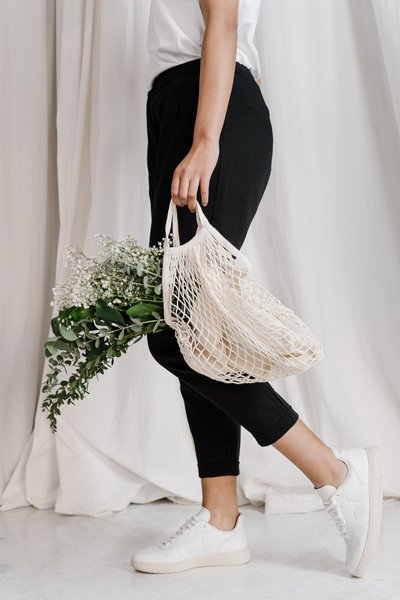 woman-in-black-pants-holding-net-bag-3738029