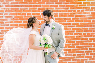 Bride and groom, Steph and Jasper face each other in front of a brick wall while Steph's veil is being blown by the wind