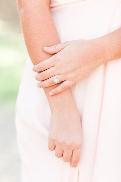 Photo to link to couples and engagement photos gallery. Photo of a girls ring on her hand while holding a blush dress