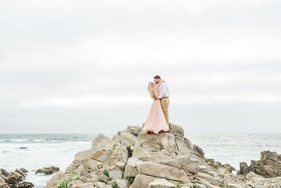 Nicole and Taylor's carmel beach engagement session. Couple kissing on cliffs engagement photo