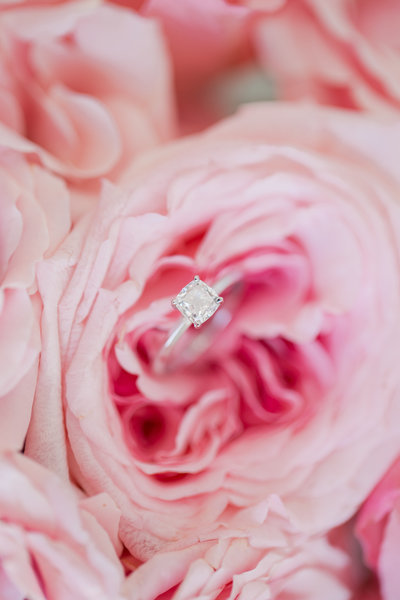 Pink peony holds a solitaire engagement ring