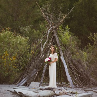 bohemian bride with flower crown, in front of a beach wood teepee, queenstown new zealand