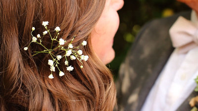bride and groom with flowers in brides hair and suit and tie tux