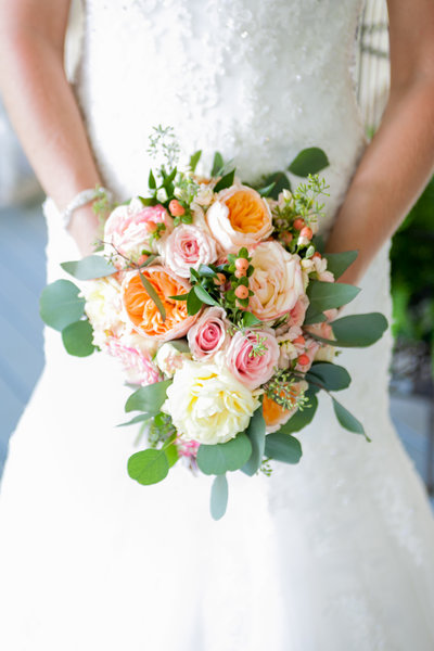 Blush and peach bridal bouquet against a white wedding dress  | Susie Moreno Photography