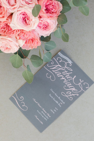 Pink peonies frame a gray and pink wedding program