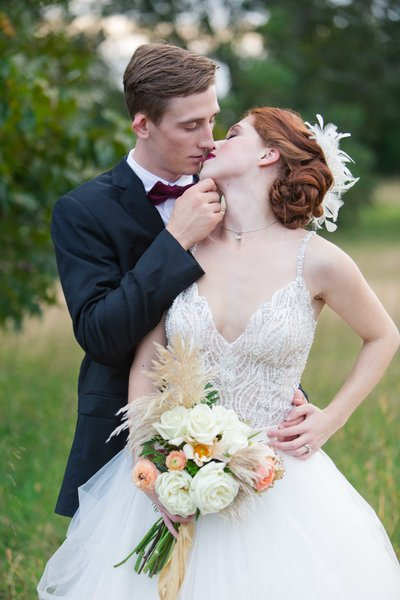 Great Gatsby wedding couple embrace in a field while almost kissing