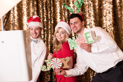 Guests pose for a photo booth picture with Santa hats on in front of a gold sequin backdrop
