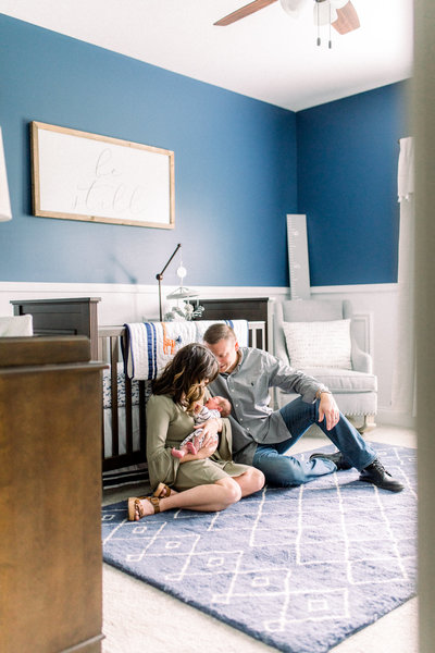 Mom, Dad and newborn baby boy snuggle up in a beautiful navy nursery in a photo by Morgan Williams Photography.
