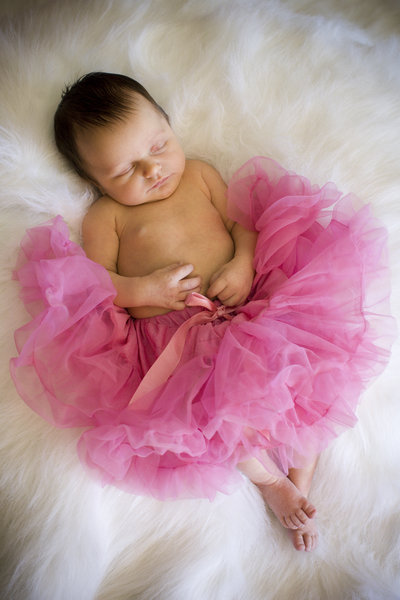 Dancing Newborn baby with pink tutu on soft white throw