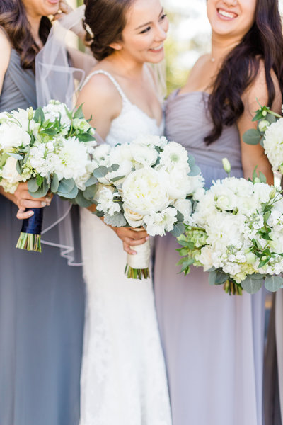 Purple and lavender bridesmaid dresses paired with soft green and white peony bouquets