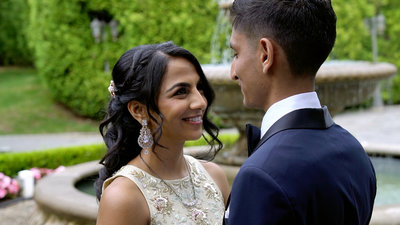 south asian bride and groom smiling at wedding venue fountain