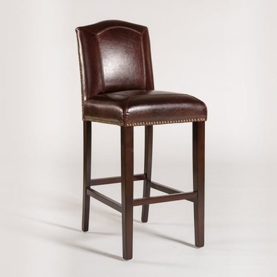 Brown leather stool with arched backrest and studded trim at Hockman Interiors