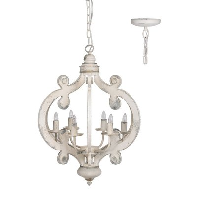 A white, wooden, hanging light fixture with ornately carved details and imitation candles from Hockman Interiors