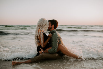 husband and wife sitting at the edge of the water kissing at sunset
