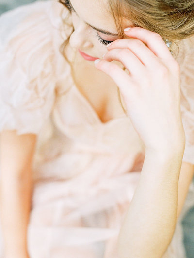 Bridal boudoir closeup of hand next to face wearing soft pink vintage dress