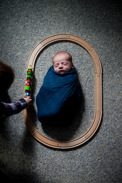 Newborn with train set and sibling lifestyle session at home