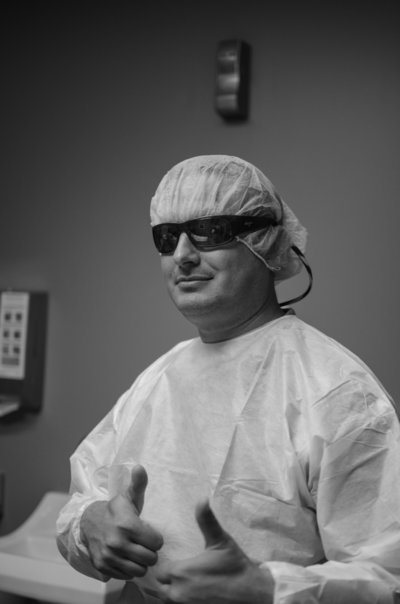 Dad wearing sunglasses and scrubs gives a thumbs up before cesarean