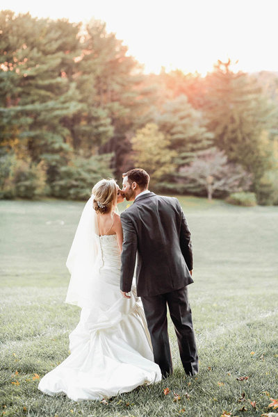 Bride and groom stand in field at sunset, Greenville Country Club, Delaware