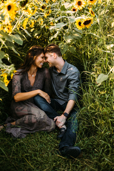 Engagement session with couple sitting in sunflower field laughing