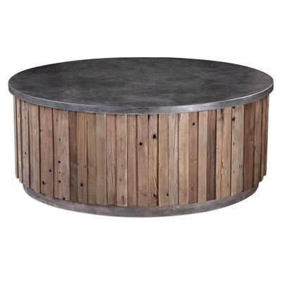 A circular, barn-style ottoman with wood sides and metal top from Hockman Interiors