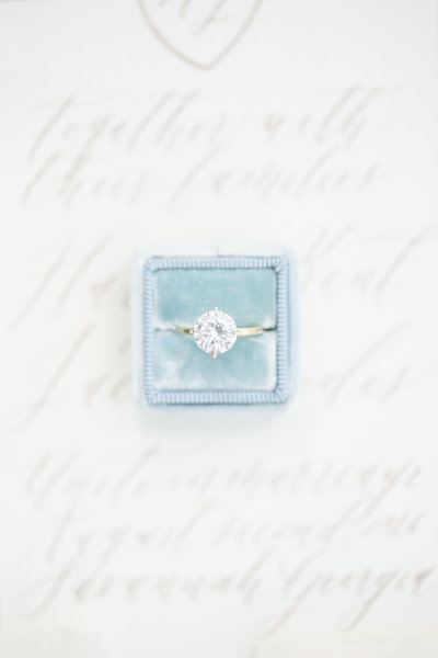 Diamond solitaire ring in a blue Mrs. Box laying on an invitation covered in calligraphy