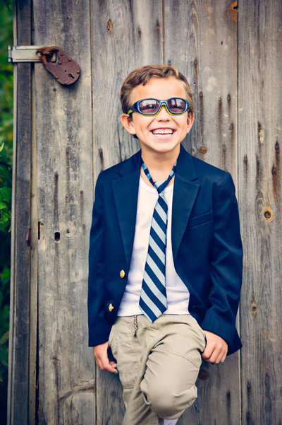 Laughing child with blue tie and blazer in natural light in San Juan Capistrano