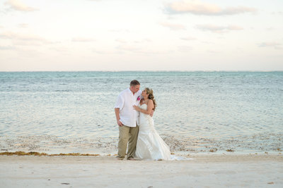 Bride and groom smile at each other during beach wedding at Mata Chica resort in Belize