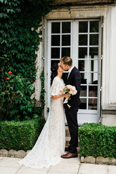 Bride and Groom kiss outside their french garden venue