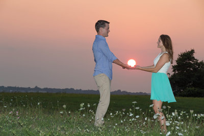engagment couple holding the sun