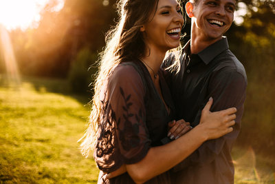 Engagement shoot backlit in sunset with laughing couple